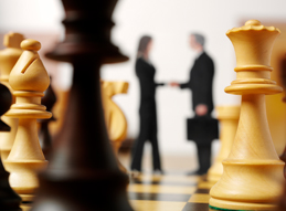 Image of Chess Pieces with two Professionals Shaking Hands in the background
