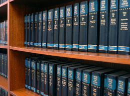 Image of a bookshelf containing two rows of dark blue law books
