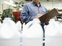 Image of an individual performing quality control task making notes with a clipboard